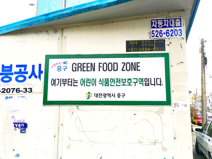 韓国 Korea Koreatown テジョン の 裏路地 Back-alley 探索シリーズ11。裏路地探索の最後はこの看板。これ、なんだと思います?実は、国が小学校の周辺半径200メートル以内を食品保護安全区域(Green Food Zone)に指定して、低栄養・高カロリーのジャンクフードと原産地が明記されていない食品の販売を禁止しているんです。すごく無いですか?日本だと、確か風営法に制限される店舗くらいですよね。更に、販売する食品に使用する食材に対する検査や衛生検査を厳しくしているんです。それだけじゃなくて、酒、炭酸飲料、スナック菓子などの高カロリーだが栄養はないという基準を設けて、ジャンクフードに健康増進負担金を賦課することを検討しているそうで。ただこれには、低所得者層がジャンクフードを食えなければ大変では無いか、との議論があったそうです。でも、市場とか伝統的な食事を出す店は、コンビニやジャンクフードよりもはるかに安価で栄養も高く、食材に至っては量は10倍以上あるんです。低所得だとジャンクフードしか食べられないという概念を植込まれることのほうが恐いなぁと思ったし、実際に課税に反対しているのはサービス業者という…日本と変わりありませんな、こういうビジネスの部分は。(;^_^A ところで、清涼飲料水の自動販売機の小学校への設置を禁止する、ファーストフードの広告をテレビで放映する時間帯を規制するという方案も検討されて実施しているみたいですが、日本だとタバコくらいですね。お酒はどうなんだろう?うーむ…悩ましい。(笑) Streetphotography EyeEm Korea Sign http://asiancorrespondent.com/2008/03/green-food-zones-questioned/