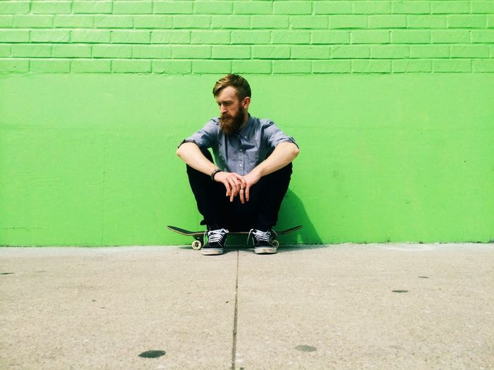 Man sitting in front of green wall