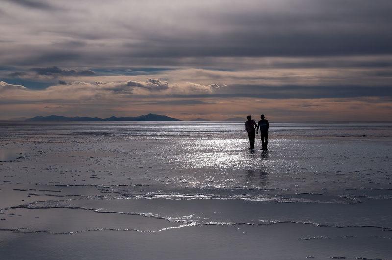 Silhouette men on beach against sky during sunset