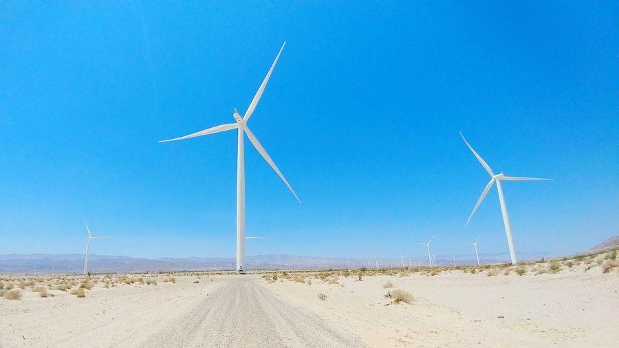 Wind turbines on land against clear blue sky