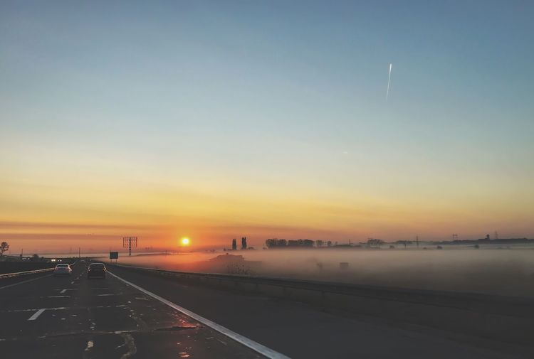Sunrise Sunrise_sunsets_aroundworld Highway Mist Misty Transportation Orange Color Car Sky Road Sun No People Scenics Land Vehicle Outdoors Nature Beauty In Nature Illuminated Water City The Great Outdoors - 2018 EyeEm Awards My Best Photo