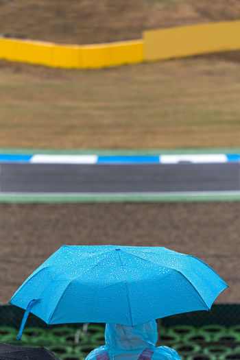 A motorsport spectator shelters from the rain under a blue umbrella and poncho in the grandstands between races. Motorsport Blue Day Focus On Foreground High Angle View Nature No People Outdoors Protection Race Track Rain Rainy Season Road Safety Security Shelter Sign Transportation Umbrella Water Wet