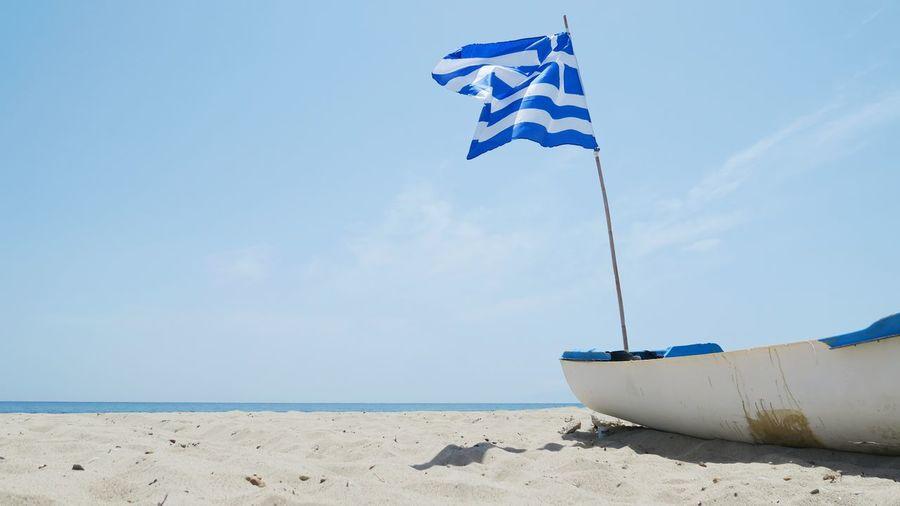 Old broken rowing boat with greece flag at nea plagia, greece Greece Nea Plagia Water Nautical Vessel Sea Beach Blue Sand Flag Wave Sky Fishing Boat Boat Coastline