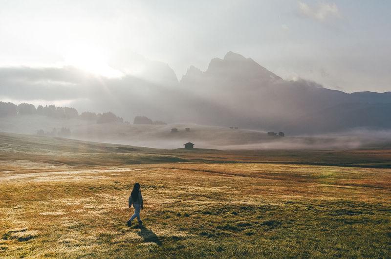 Woman walking on field against sky