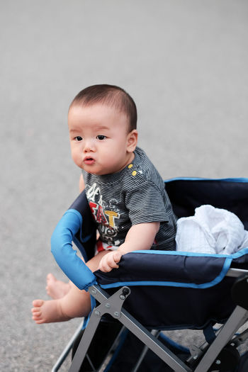 Cute Baby Sitting In Baby Stroller Outdoors