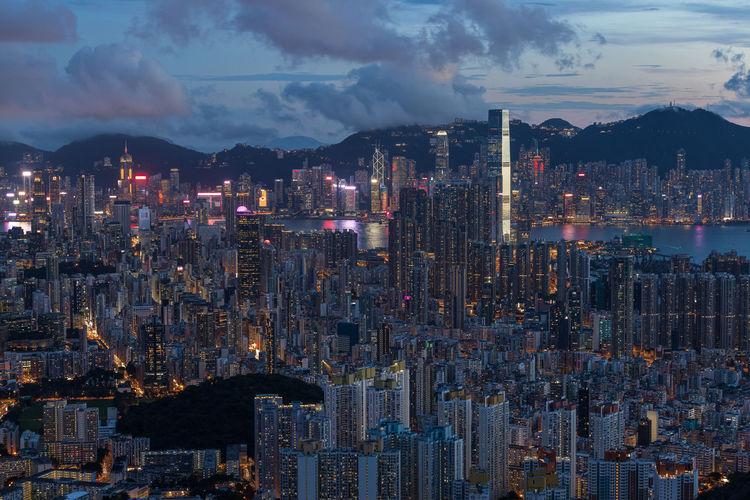 Illuminated cityscape against sky at magic hour