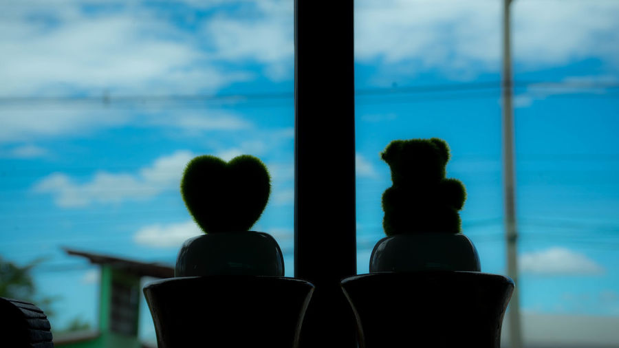 Close-up of silhouette people by window against sea