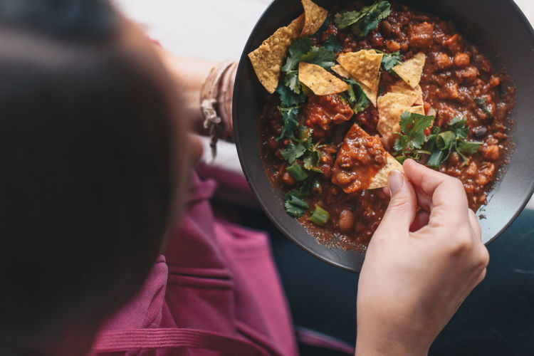Young woman eating mexican food Chips And Salsa Cilantro Close-up Day Food Food And Drink Freshness Healthy Eating Human Body Part Human Hand Indoors  Mexican Food One Person Plate Ready-to-eat Real People Salsa Vegetable Women