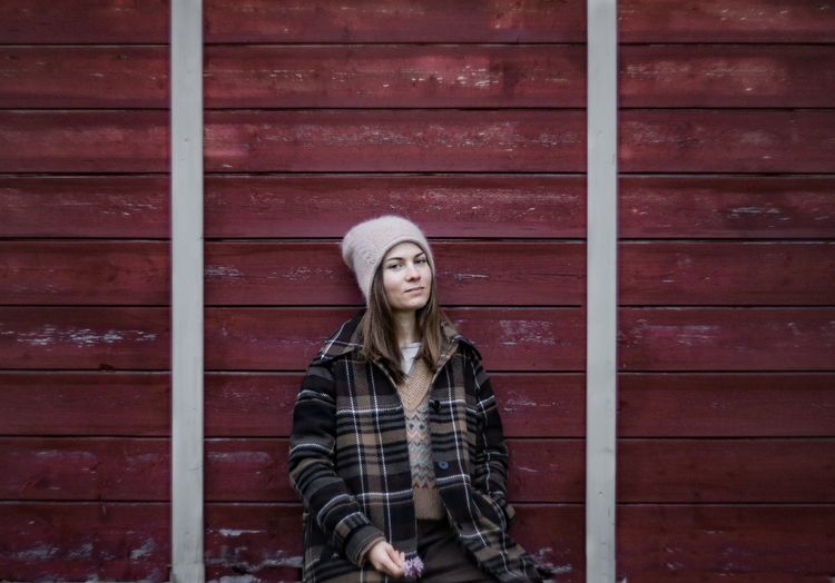 Portrait of young woman standing against brick wall