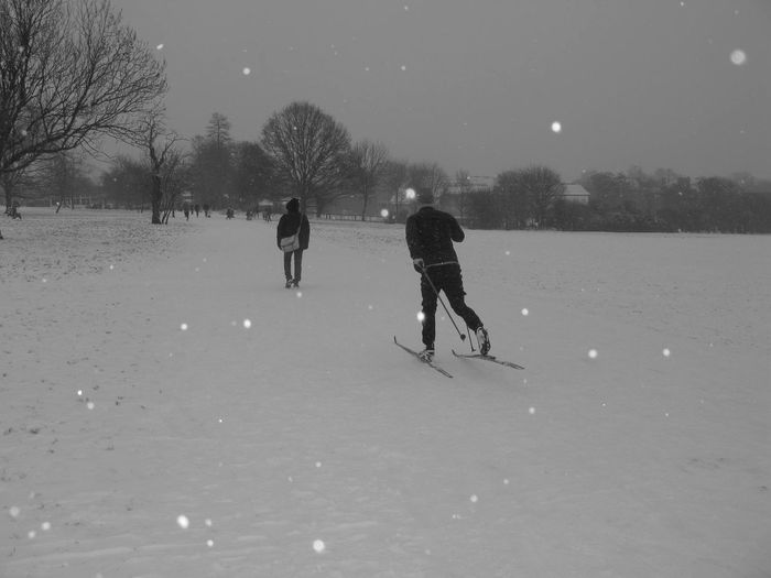 Hampstead Heath Cold Temperature Cross Country Skiing Grey Sky Greyscales Leisure Activity Men Motion Outdoors Real People Rear View Snow Sport Two People Warm Clothing Winter Winter Sport