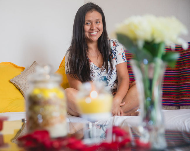 Portrait of a smiling young woman sitting at home