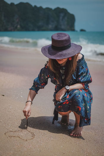 Drawing a heart One Person Real People Beach Women Water Land Full Length Leisure Activity Nature Lifestyles Clothing Day Hat Sunlight Casual Clothing Adult Sand Focus On Foreground Outdoors Hairstyle Krabi Krabi Thailand Heart Drawing
