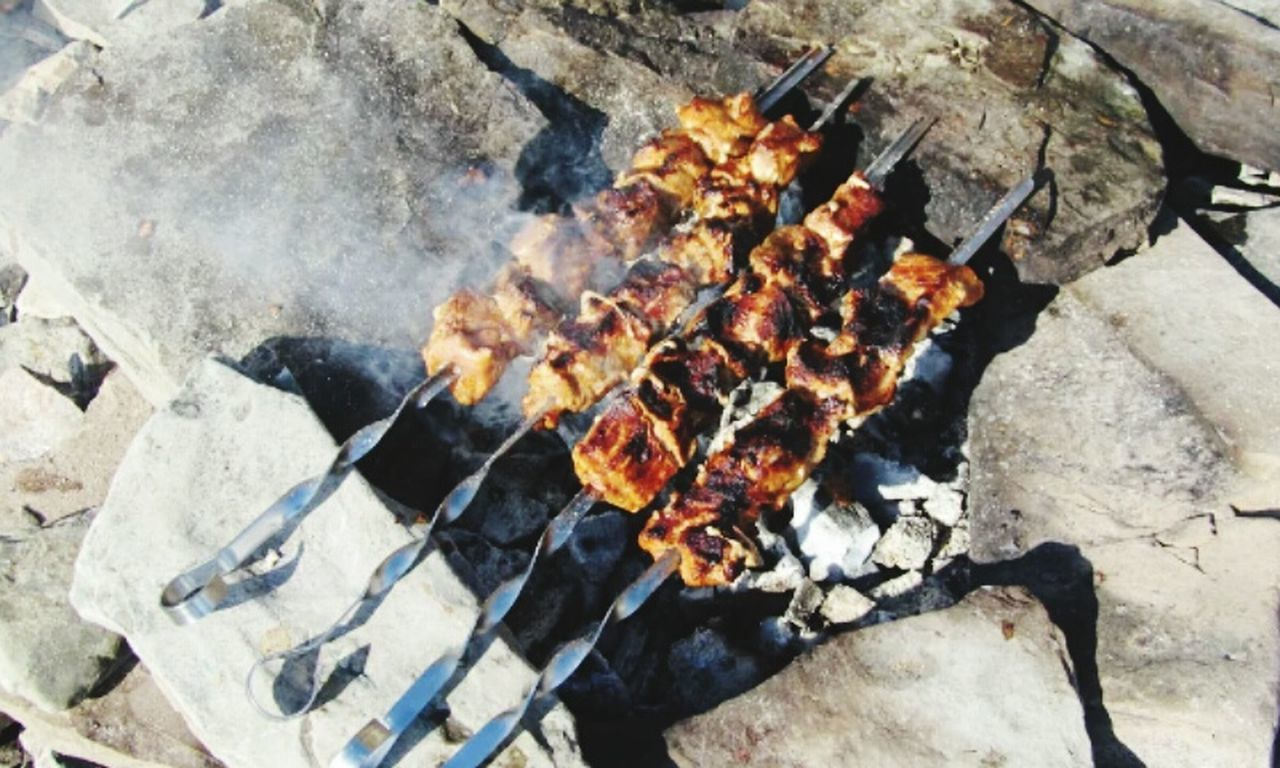 heat - temperature, barbecue grill, flame, barbecue, burning, outdoors, coal, grilled, preparation, day, high angle view, smoke - physical structure, food and drink, no people, meat, close-up, fire pit, ash, nature, freshness