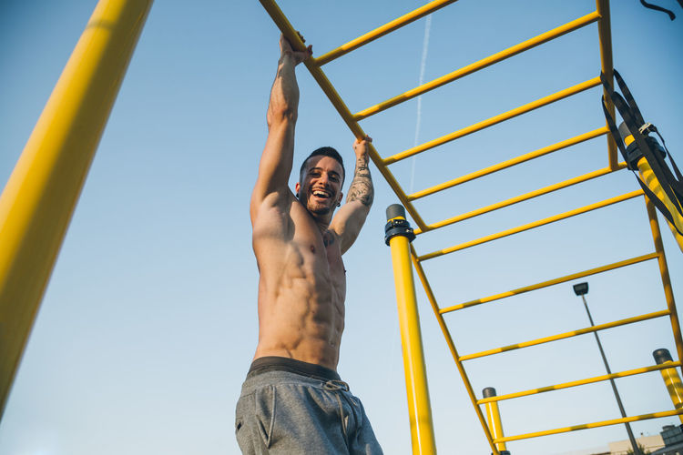Portrait of smiling shirtless man jumping against sky