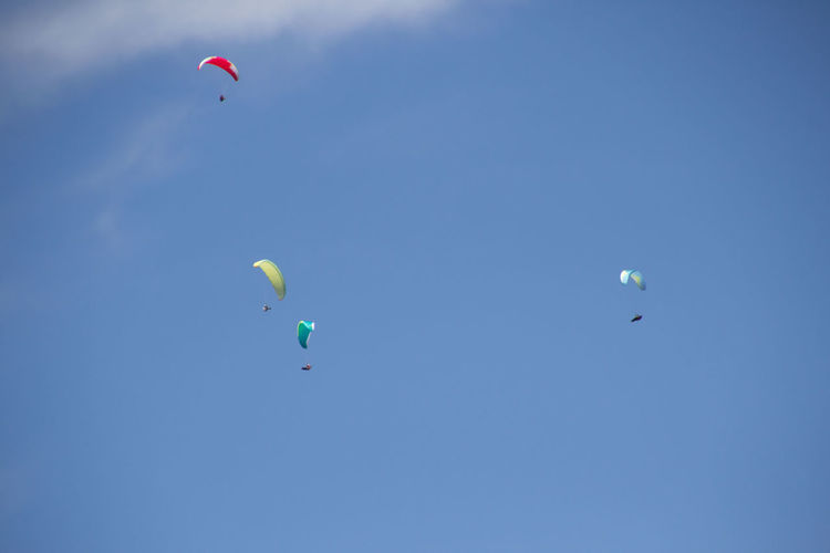 Low angle view of people paragliding against clear blue sky