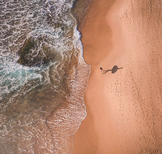 High Angle View Of Woman Carrying Surfboard On Shore At Beach