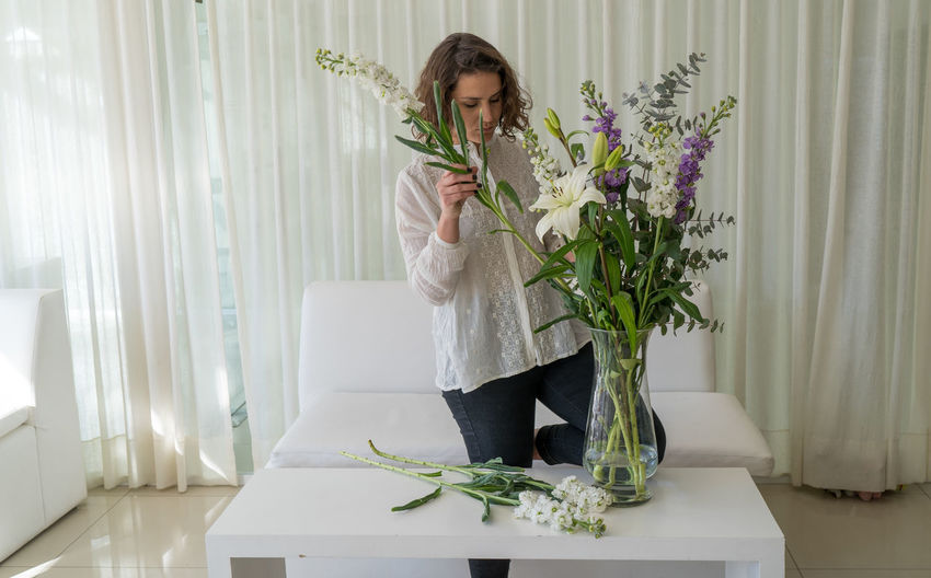 Young woman holding white flower at home