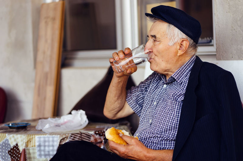 Senior man having food and drink while sitting on seat