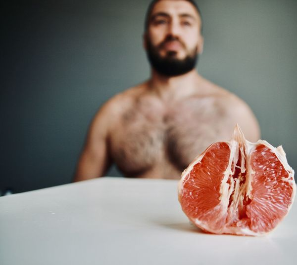 Midsection of man with ice cream on table