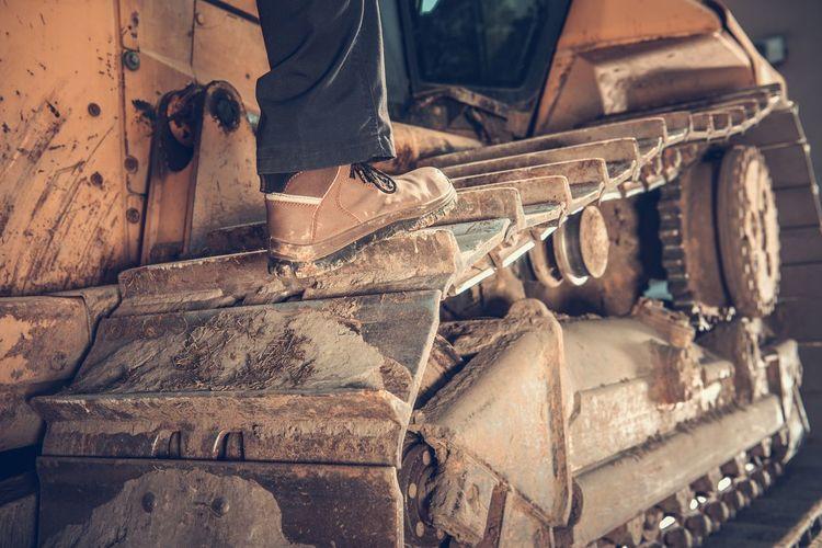 Low section of man on bulldozer wheel