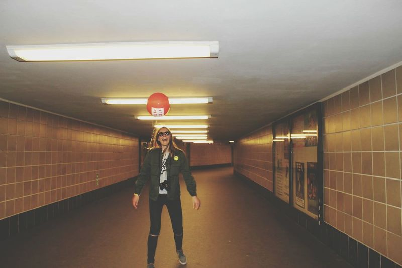 Full Length Of Cheerful Woman With Helium Balloon In Illuminated Tunnel