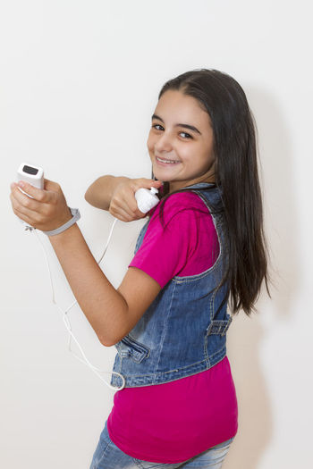 Video Games Beautiful Woman Casual Clothing Communication Connection Console Emotion Happiness Holding Indoors  Leisure Activity Looking At Camera Mobile Phone Mp3 Player Music One Person Portrait Side View Smiling Technology Three Quarter Length White Background Wireless Technology Young Adult