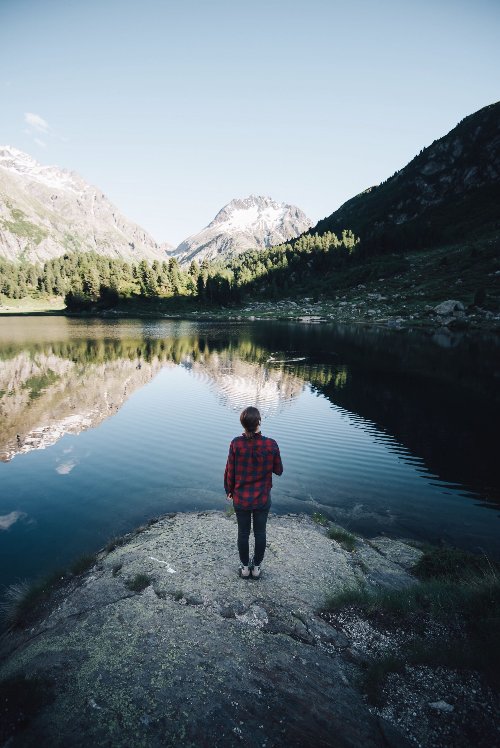 reflection, rear view, lake, full length, water, one person, one man only, nature, leisure activity, only men, beauty in nature, sky, men, people, grass, adults only, outdoors, mountain, young adult, day, adult