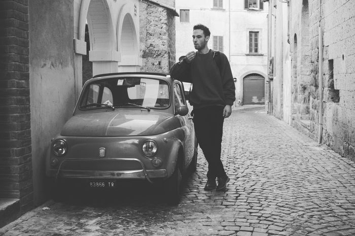 Smoking a cigerette; leaning on a small car in Italy Only Men Adults Only One Man Only Car One Person Casual Clothing Transportation Full Length Men Standing Adult City People Portrait Day Young Adult Outdoors CigerettePortraits Car