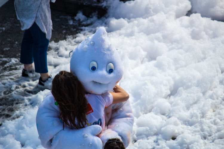 Girl Embracing Snowman During Winter