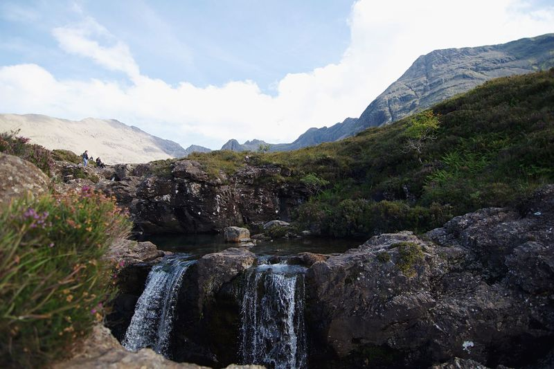 Scenic view of waterfall and mountains against sky