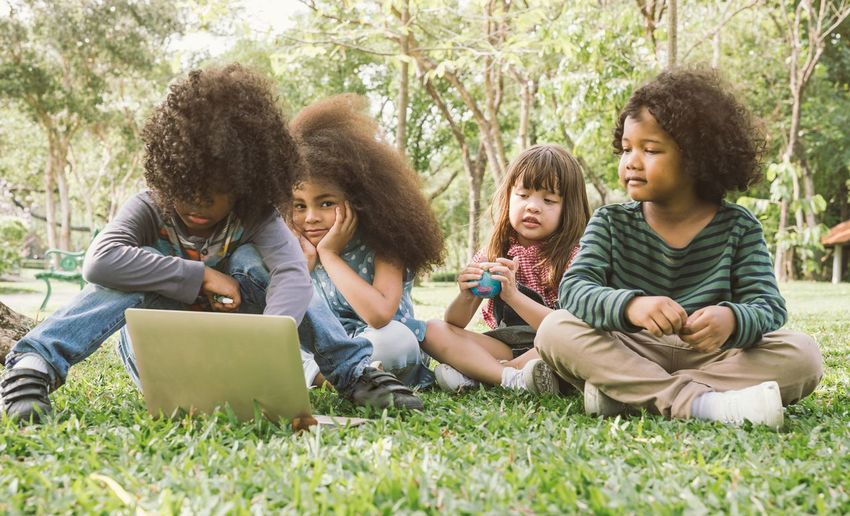 Friends With Laptop Sitting On Grassy Field In Park