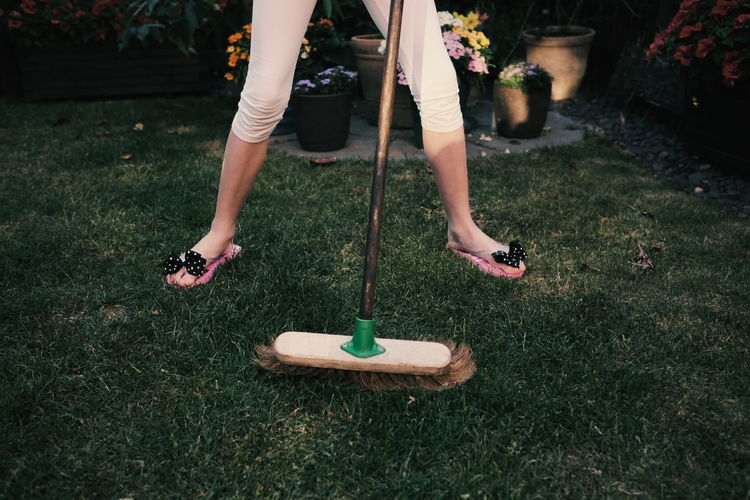 Low section of woman standing with gardening equipment on grass at back yard