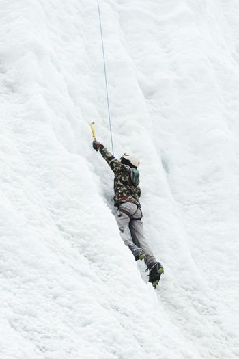 Low angle view of man climbing on snowcapped mountain