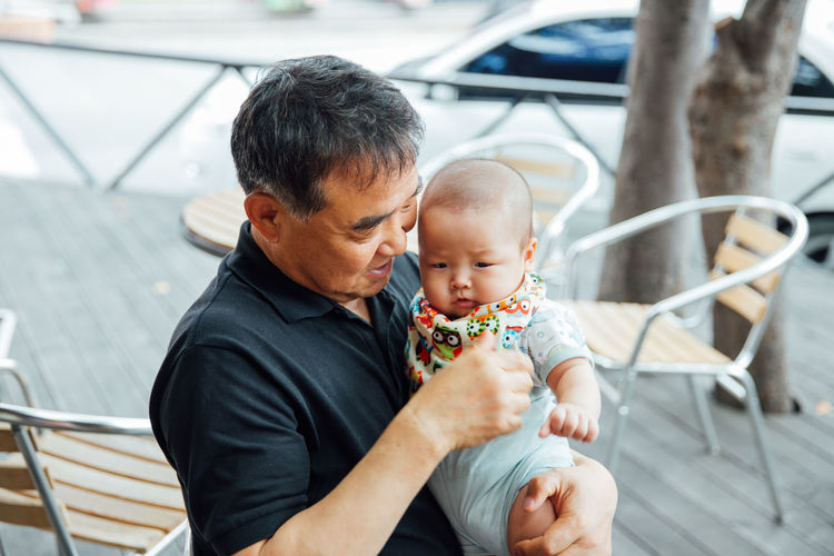 Grandfather holding grandson in porch