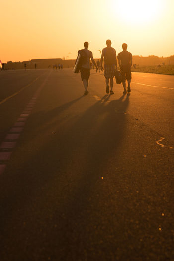 Rear View Full Length Of Friends Walking On Road Against Sky During Sunset