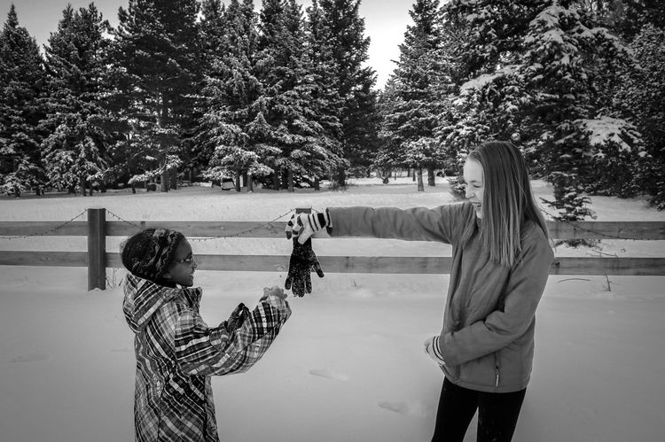 Playing Snow Children Bonding Casual Clothing Childhood Communication Day Friendship Human Hand Leisure Activity Lifestyles Nature Outdoors People Photographing Real People Rear View Sibling Standing Technology Togetherness Tree Two People Warm Clothing Women Young Adult Young Women