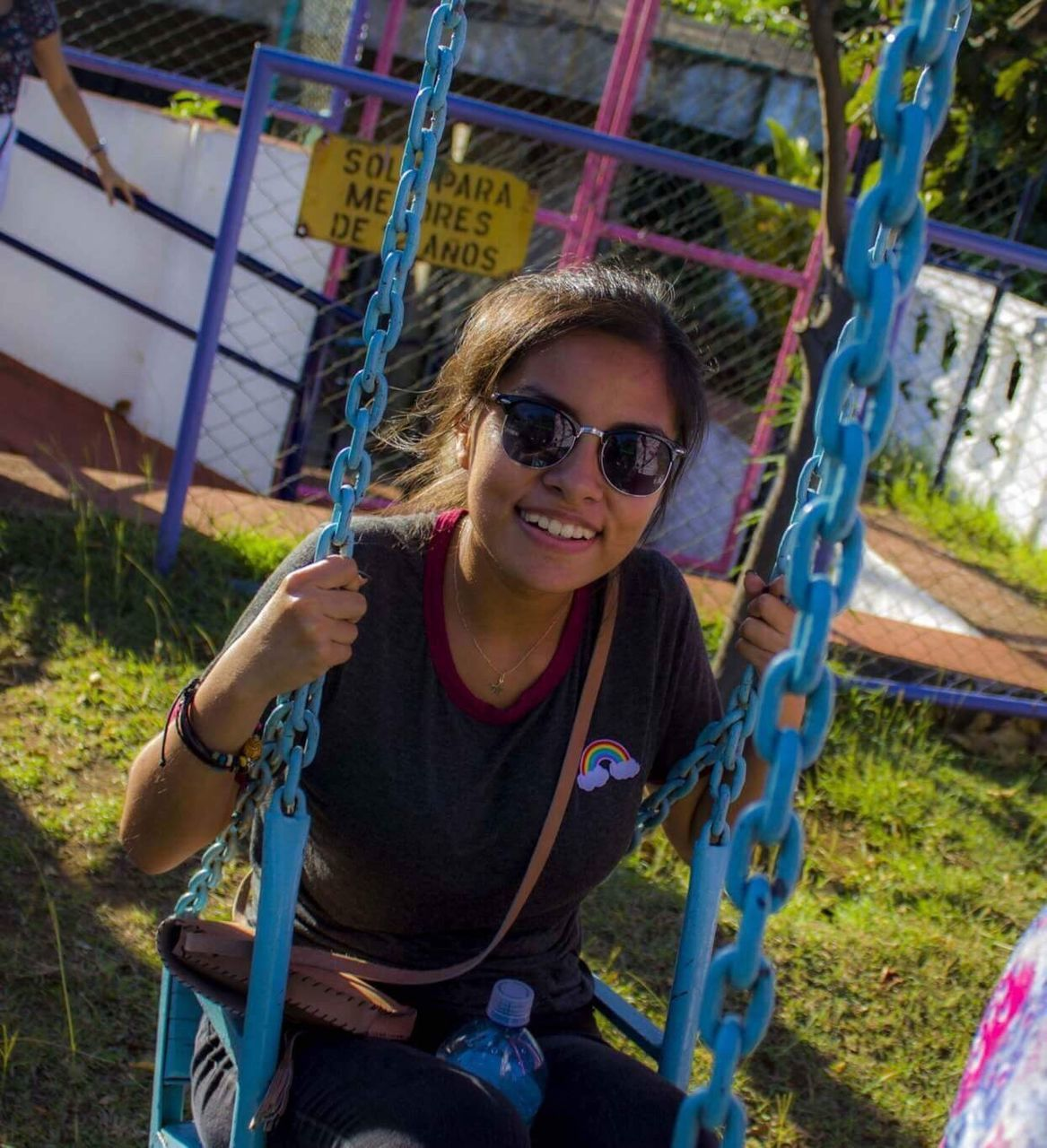 sunglasses, smiling, looking at camera, young adult, one person, casual clothing, leisure activity, young women, outdoors, front view, real people, lifestyles, day, happiness, portrait, chain, swing, people
