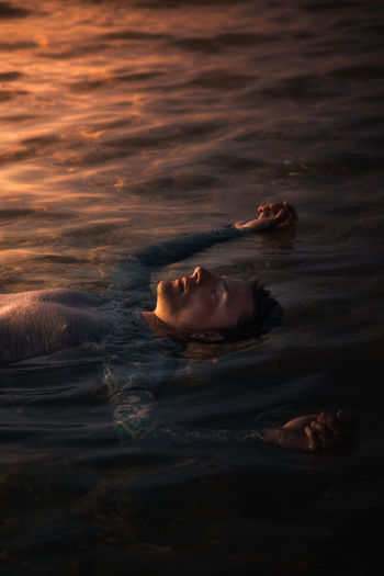 Man floating on water at sunset