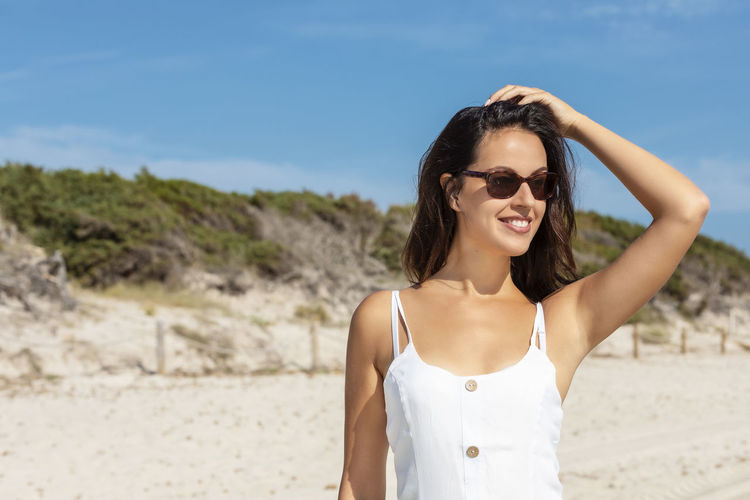 Portrait of young woman wearing sunglasses standing on beach