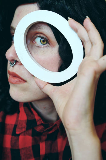 Close-up portrait of young woman looking through object