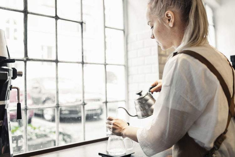 Side view of man holding coffee while standing by window