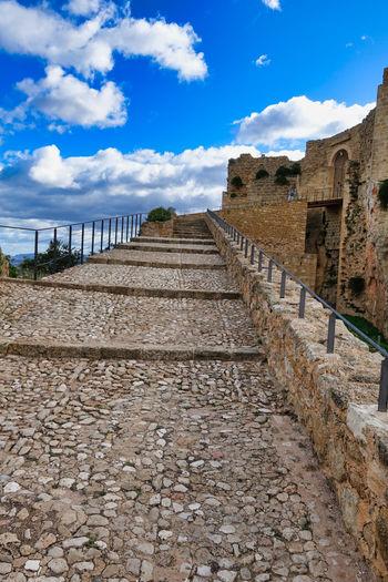 Footpath by wall against sky