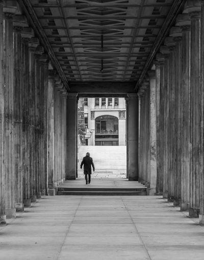 Rear view of man walking in colonnade