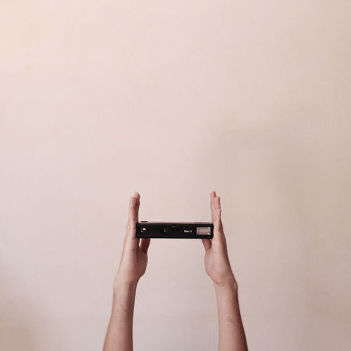 Cropped hands holding camera against wall