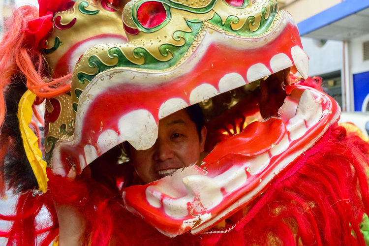 A man inside a dragon's head looking at the camera. The Chinese community in Madrid celebrated the Chinese New Year of the Monkey in the Usera district of Madrid, Spain. Celebration Chinese Chinese Holiday Chinese New Year Chinese New Year 2016 Colours Dragon Editorial  Happy Parade People Portrait Red Smiling Year Of The Monkey