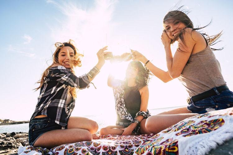 Cheerful friends on beach against sky