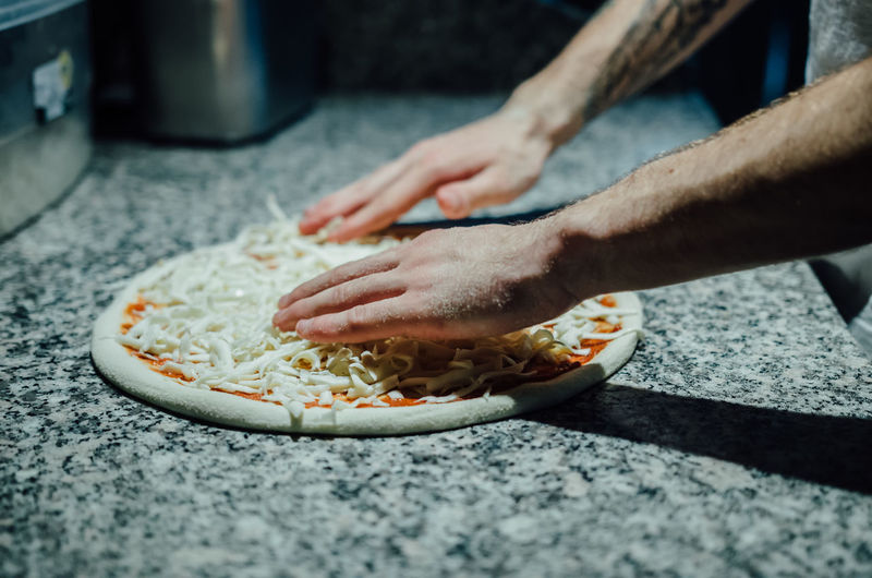 Cropped image of chef preparing pizza at kitchen counter