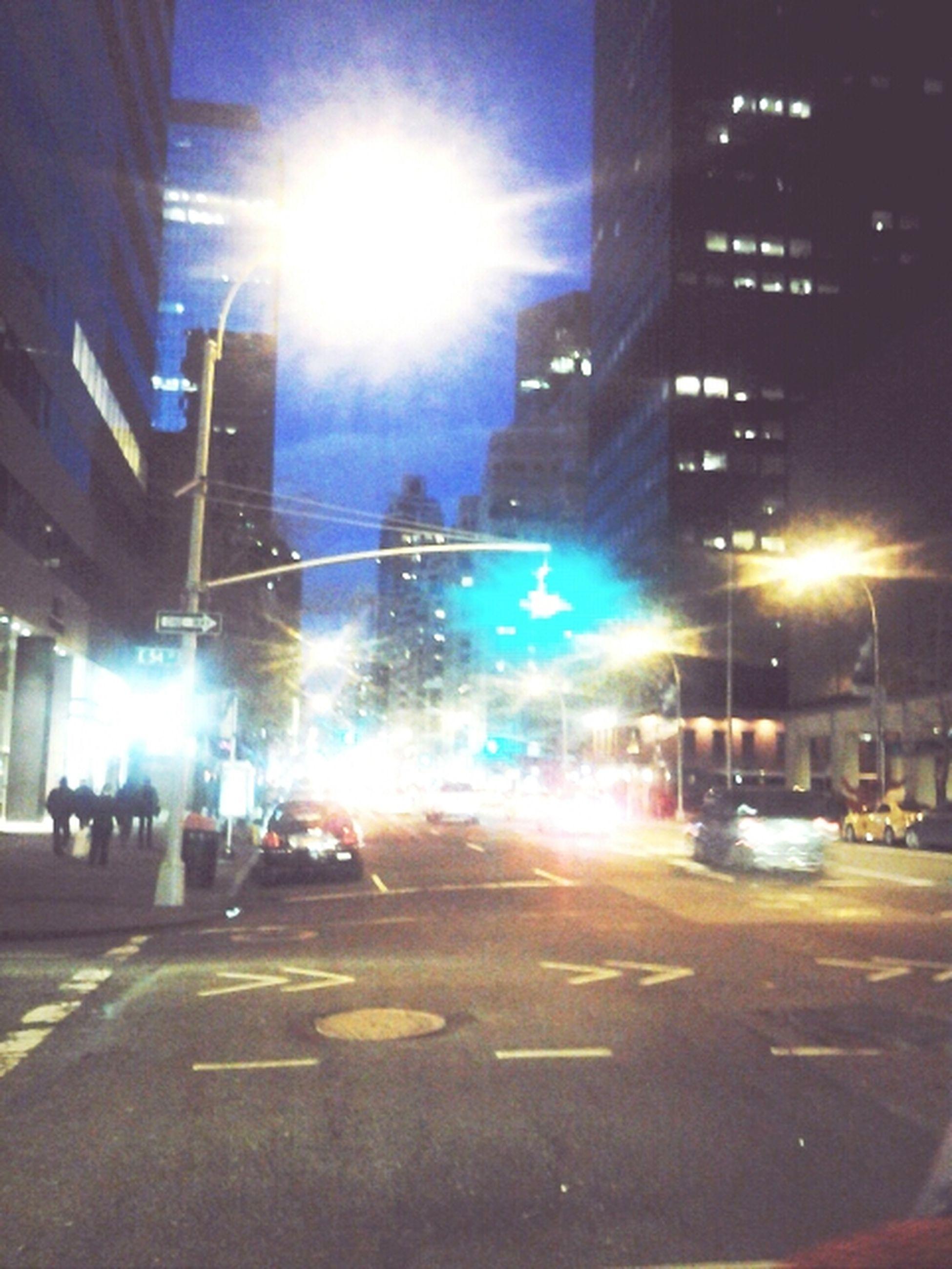city, transportation, building exterior, street, architecture, car, built structure, city street, illuminated, land vehicle, road, city life, street light, mode of transport, road marking, night, traffic, road signal, lens flare, zebra crossing