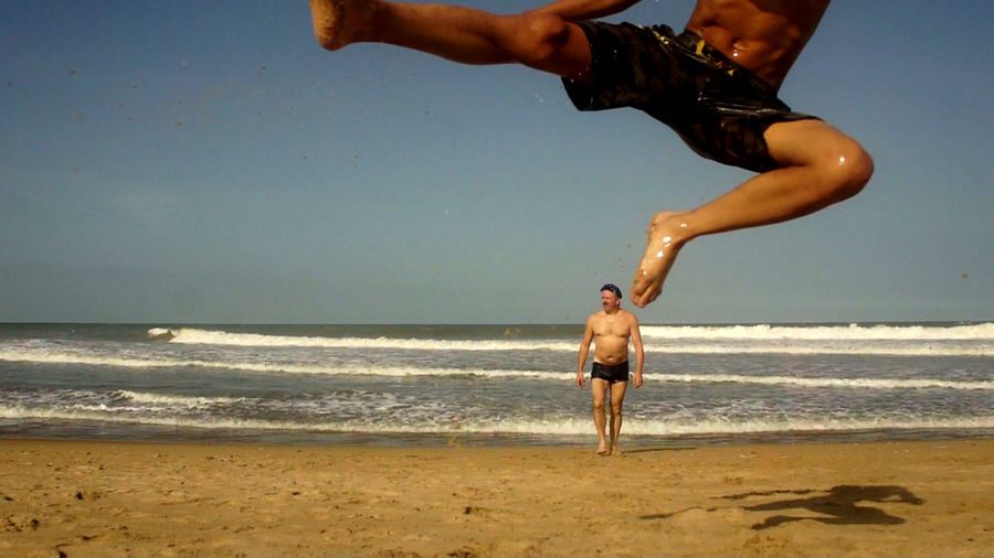 Son jumping while father walking at beach against clear sky