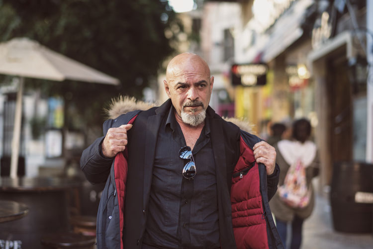Bald businessman wearing winter coat while walking in city